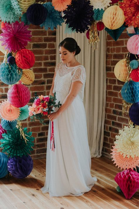 This styled shoot was an explosion of colour with a backdrop of a rainbow wedding arch made from paper honeycombs and pinwheels. Click through for more colourful wedding inspiration. #colourfulweddings #weddingideas #weddinginspiration #rainbowwedding #handmadeweddings #rachelemmastudio #paperflowers #weddingbackdrop