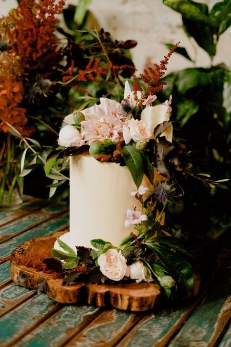 A classy, modern wedding at Glasshaus warehouse in Melbourne, Australia - absolutely full of lush greenery. The cake is a tall, modern vanilla cake with lots of lush flowers and decorations on a raw, wooden stand. Wedding cake decorations ideas and inspiration.