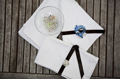 Go simple with plain white napkins that dazzle when dresses up with a beautiful brooch.
