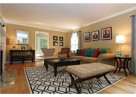 Fun decorating with splashes of color from the art. Cool geometric carpet to tie in the modern theme of this living room.