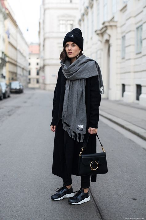 a total black look with skinnies, a midi coat, a beanie, trainers, a bag and a large grey scarf