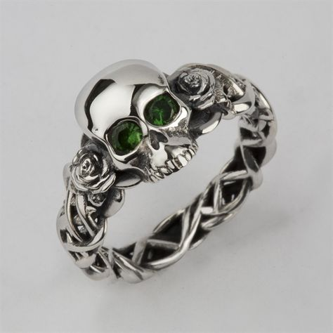 Bespoke Skull wedding ring custom made in solid silver with green tsavorite eyes. This design was commissioned for the customers wife. The green eyes really shine.. This is a great design, with the softness of the metal and stones juxtaposed with the scary skull and spiky thorns, fabulous!