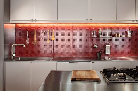 This striking red backsplash doubles as a pegboard for hanging cookware. Courtesy of Matt Delphenich.