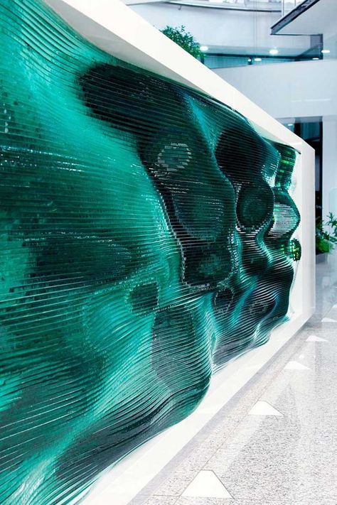 Designer Tamás Ábel in association with Architects, has created a wavy layered glass panel for the front reception desk in the EMKE office building, located in Budapest, Hungary. The front of this reception desk was made by stacking layers of glass o