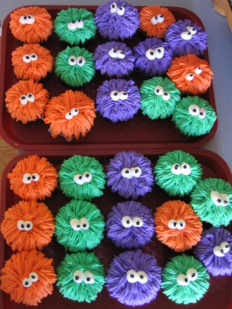 """Monster Cupcakes.  She used the """"grass"""" tip. Just start from the outside of the cupcake and work inward. Then add the eyes."""