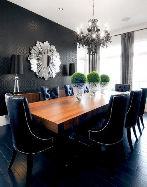 chic black dining room design with black walls paint color, chunky wood modern dining table, black leather tufted dining chairs with nailhead trim, sunburst mirror, black Kelly Wearstler imperial trellis wallpaper, charcoal gray silk drapes and matte ebony wood floors.