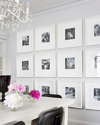 Lots of square frames in a gallery wall, white, black, and pink dining room