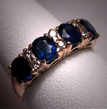 A Gorgeous Antique Ceylon Sapphire Diamond Wedding Ring, Vintage Art Deco, circa 1920-30's in 18K Gold. The center of this estate ring holds four quality ceylon blue faceted sapphire gemstone measuring about 4 x 5 mm oval. There are six sparkling white diamonds as well. The setting is 18K gold with lovely antique detailing