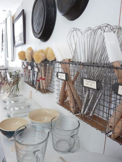 Racks on the wall of the kitchen for easy access to utensils like wooden spoons,