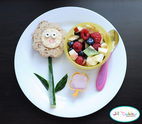Sandwich cut into flower shape. Rice cracker face with marshmallow eyes. I used food safe markers to draw on the details. Cucumber stem. Fruit salad with a small container of yogurt for dipping.