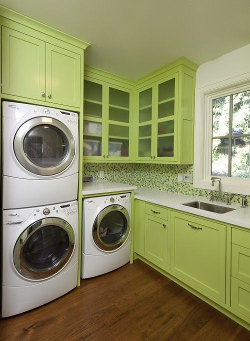 Bright green laundry room design with white washer & dryers, green cabinets and green mosaic tiles backslash.
