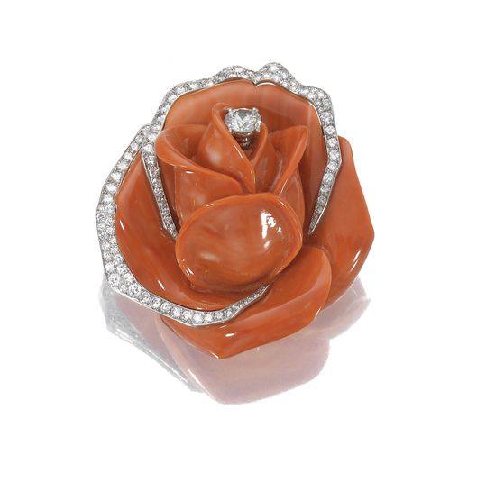 CORAL AND DIAMOND BROOCH, CARTIER,  CIRCA 1960.  Designed as a  carved coral rose, the centre and edges of the petals highlighted with circular- and single-cut diamonds, mounted in platinum and gold, signed Cartier Paris and numbered, French assay and maker's marks, accompanied by fitted case.