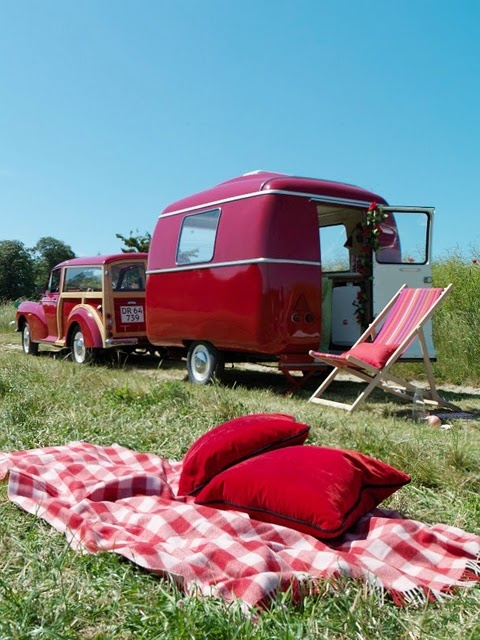 Red car, red travel trailer, red gingham blanket and red pillows