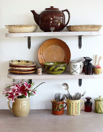 Open shelves in the kitchen hold antique Mexican and French ceramics and mugs by ceramist Karen Donleavy.