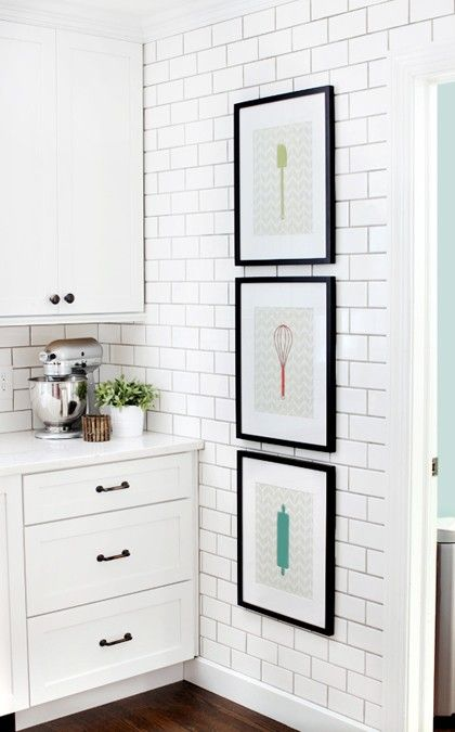 Framed prints in the  kitchen / white subway tile