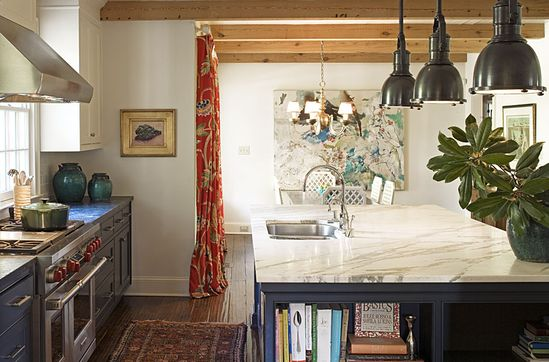 A Barrie Benson kitchen, dark cabinets, marble counter tops, houseplant, pendent lights, old rug, turquoise art, red curtains, exposed wood ceiling beams