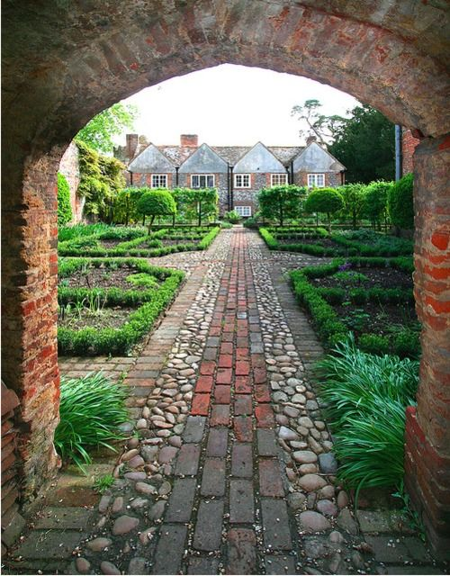 Formal geometric garden brick archway stone and brick path