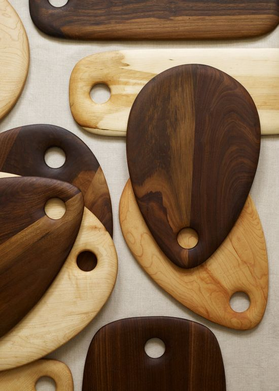 Handmade wooden cutting boards double as striking serving platters for a modern rustic table setting.