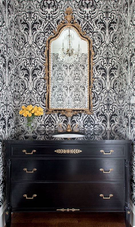 Bold wallpaper, black dresser-style sink, antique mirror, hardwood floors