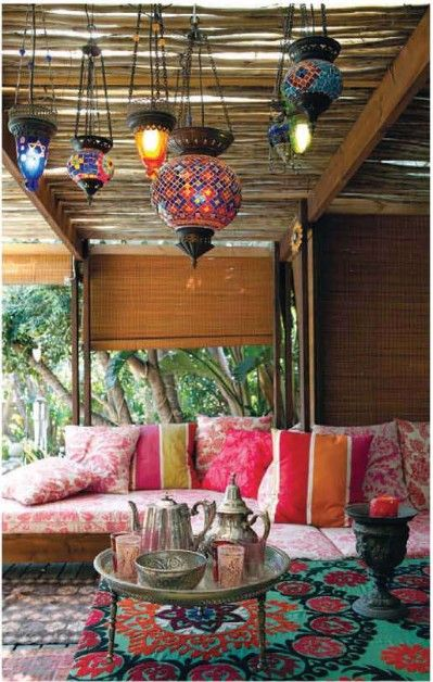 Outdoor room with Moroccan theme: daybed couches, colorful pillows, silver tea set with Moroccan glasses, and Moroccan lanterns hanging from branches over pergola.