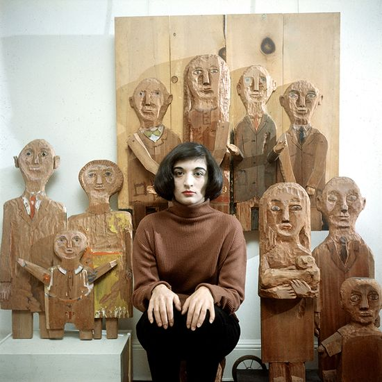 Portrait of French-born artist Marisol Escobar- poses with some of her carved wooded sculptures. New York, New York, 1958