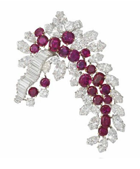 A RUBY AND DIAMOND 'GRAPPE' CLIP BROOCH, BY BOUCHERON.  Modelled as a stylised spray, the oval and circular-cut ruby centre to a marquise and brilliant-cut diamond cluster surround, with undulating baguette-cut diamond vine, circa 1950, French marks for gold, 6.2cm long Signed Boucheron, no.1144062