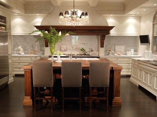 Kitchen with white cabinets with dark wood island