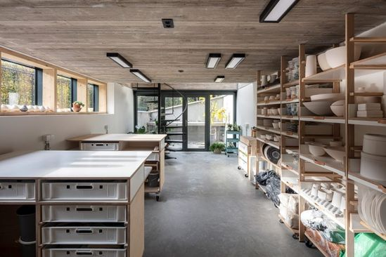 In this workshop, concrete covers the floors and wood slabs run across the ceiling, peppered with rectangular, black lights.  Wood furniture pieces in the space, including the two desks on wheels and the shelving unit, were custom-built for the project.