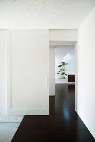 mod barn style door. dark, dark floors, white walls.