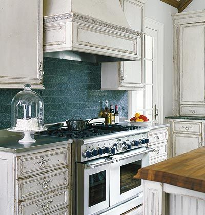 Any stone available as counter slabs can also be had in tile form -- and is often drastically cheaper per square foot. Here the honed granite from the kitchen's perimeter counters repeats as a backsplash.