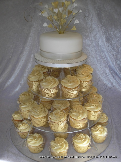 Wedding cake and cupcake tower with ivory top tier cake and ivory buttercream cupcakes decorated with gold hearts and wrapped in a gold cupcake wrappers Topped with a feathered gold and white heart wired cake topper... Wedding ideas for brides, grooms, parents & planners ... itunes.apple.com/... … plus how to organise an entire wedding, without overspending ? The Gold Wedding Planner iPhone App ?