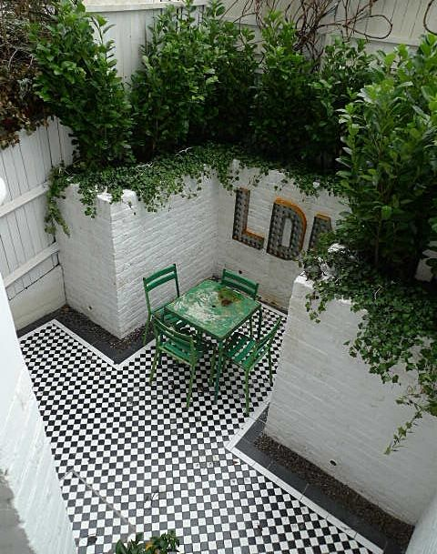 mosaic+courtyard+garden+with+white+walls+black+and+white+tiles+and+soft+planting.