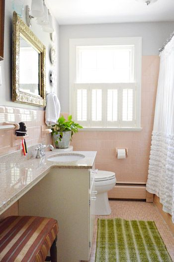 Work with whatcha got.  Pink tile in the bathroom you say?  Make it girly and fun with an ornate mirror and add some white and lime green.  It's actually pretty awesome...