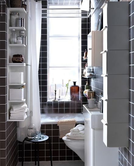 Even in a teeny tiny space you can achieve a lot with some clever floating shelving and vertical storage units. Just keep it off the floor and neutral so the eye doesn't stop there. #black-tiles #bathroom #small_apartment #storage