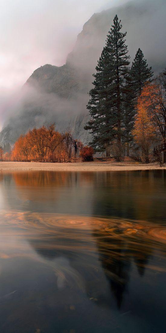 Leaves swirl at sunset in a light November rain on the Merced River in Yosemite Village, California • photo: Joe Ganster on Flickr
