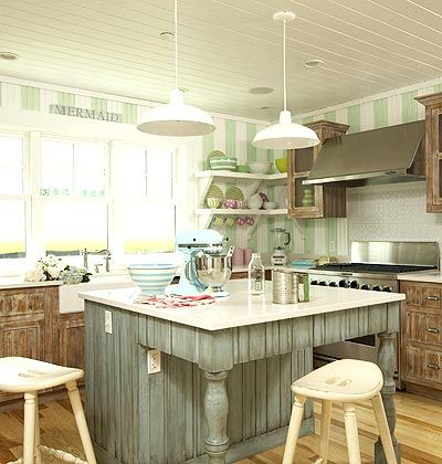 A coastal kitchen with green and white striped walls. Distressed cabinets, pale green, striped beaded board walls contrast the sea blue color with antique rub in the island.