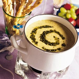 Fondue is fun! This contemporary appetizer recipe is flavored with pesto and three cheeses.