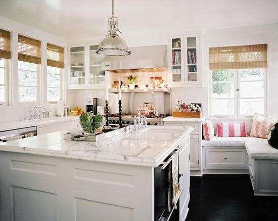 An open white kitchen with a center island and a corner bench