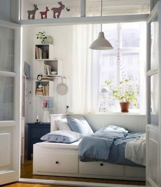 Tiny bedroom- bed turned sideways against wall with drawers