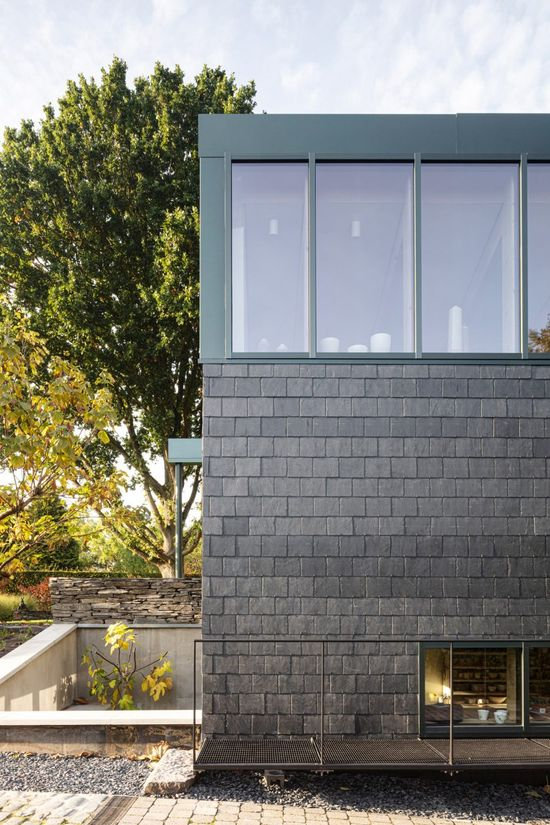 Architect Bruno Stevens has added a sunken slate-clad ceramics studio to a house on a sloping site in Belgium.