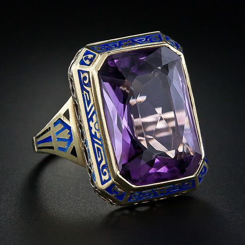 An intriguing and sizable Art Deco ring, circa 1930s. A bright purple, faceted emerald-cut Amethyst is regally presented in a distinctly green gold mount ornamented with striking blue and black enamel. Elaborate engraving adorns the under gallery.