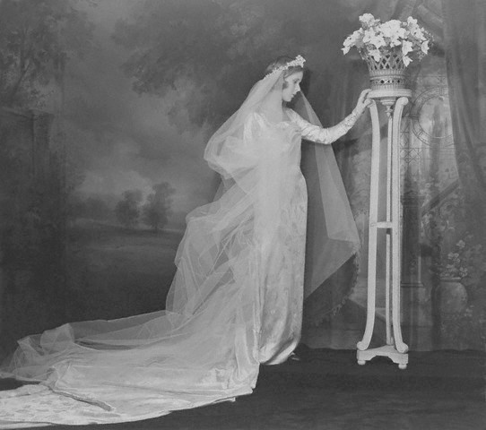 1937  photo by Cecil Beaton of Priscilla St. George wearing her wedding gown, a brocaded white satin gown with a long train and a tulle veil.