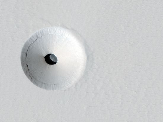 A Gigantic Circle of Mars Sand around a Large Mars Hole.  Black spots have been discovered on Mars that are so dark that nothing inside can be seen.... The above hole is about the size of a football field and is so deep that it is completely unilluminated by the Sun. What created this unusual hole in Mars? The hole  discovered by chance on images of the dusty slopes of Mars' Pavonis Mons volcano taken by the HiRISE instrument aboard the robotic Mars Reconnaissance Orbiter currently circling Mars