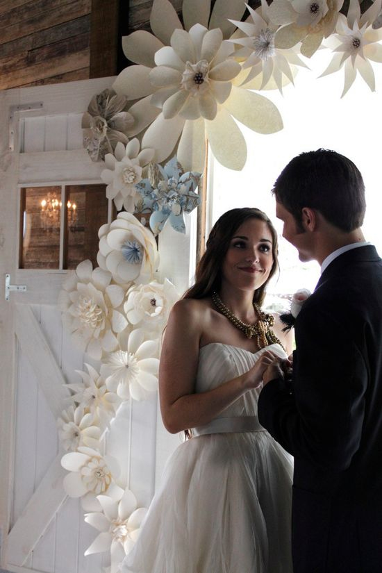 Less paper flowers (like in corners only) and put on wood arch.. and have pops of teal or other wedding colors if wanted.