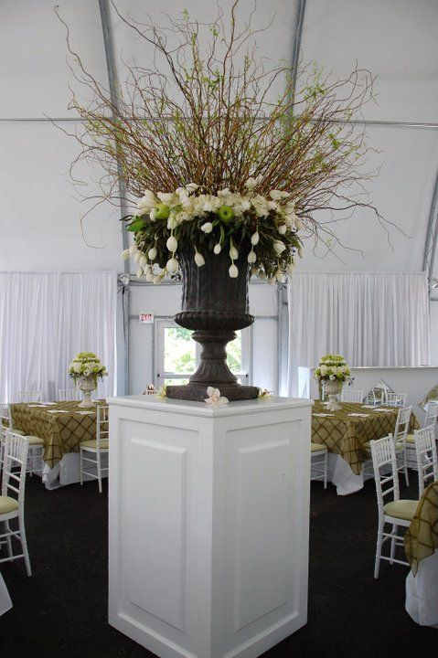 urn floral arrangement   The center of this room featured a large greystone urn with a bursting arrangement of sprouting curly willow branches with a broad collar of whit hydrangea and hundreds of cascading white French tulips. So beautiful.  www.Penncora.com