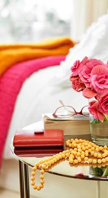 bedside table styling in bright pinks, oranges and yellows