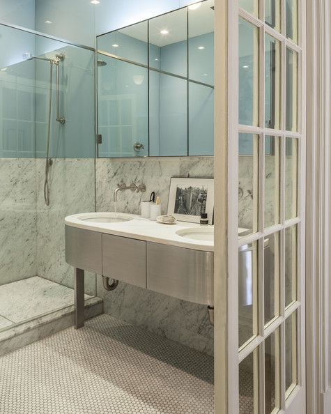 Bathroom - Penny-tile flooring and marble walls in a sleek bathroom
