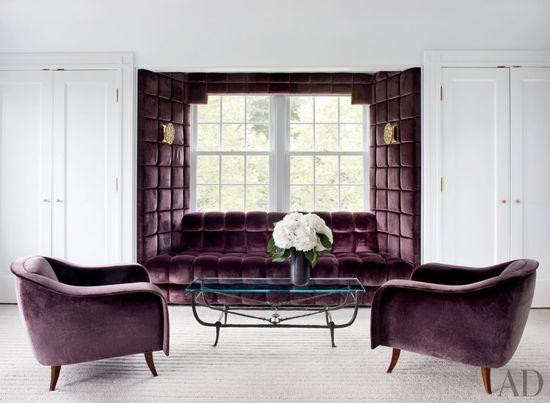In a Greenwich, Connecticut, living room, the window seat and Joaquim Tenreiro chairs are covered in a purple Sahco velvet.