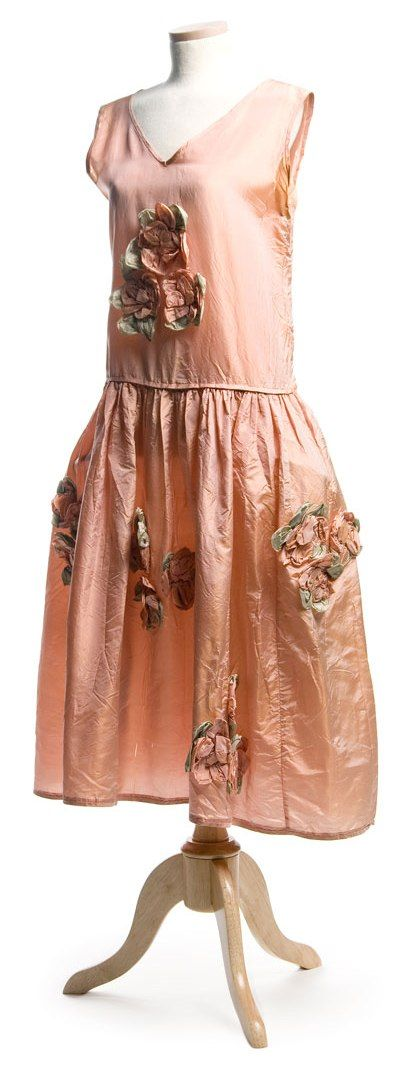 Robe de style: ca. 1920's, silk, ornamented with silk rosettes, the full, gathered skirt has sewn in hip panniers.