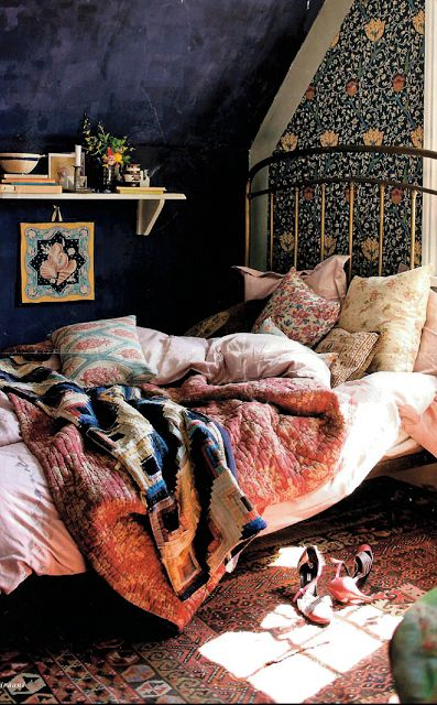 coziness, dark bedroom, layered bedding, vintage rug, wallpaper accent wall